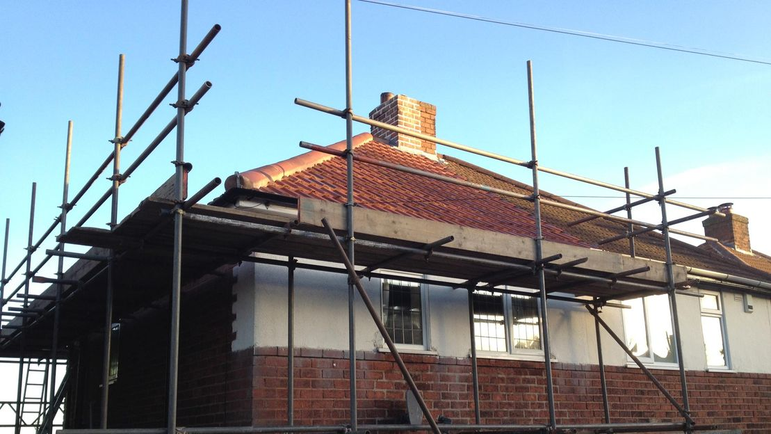 Scaffolding around a house to aid with roofing reapirs
